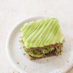 cucumber tempeh sandwich on a white plate